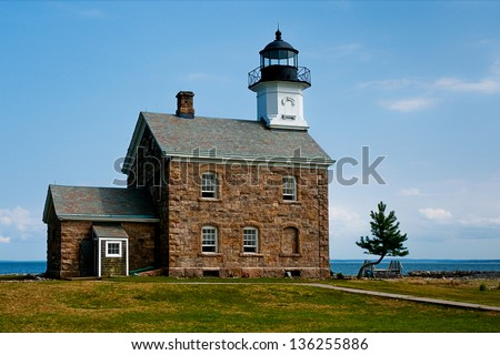 Sheffield Island lighthouse had a keeper who had farm animals that would cross over to nearby islands and become stranded, leaving the keeper to constantly try to keep the animals on the island. - stock photo