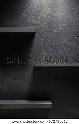 shelf and black wall on wooden background