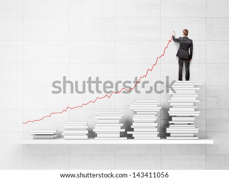 shelf with books and businessman drawing rising graphs