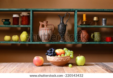 Shelf with various things and fruits on the table - stock photo