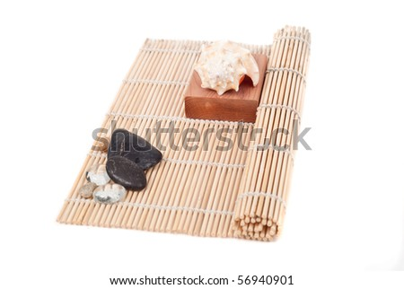 Shell on Wood Block On Top of Sushi Roller - stock photo