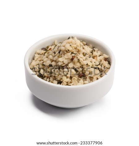 shelled hemp seeds in a round bowl isolated on white - stock photo