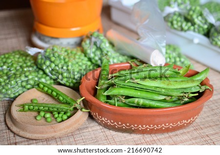 Shelling peas, measurement, packing and preparation for deep freezing for the winter stores - stock photo