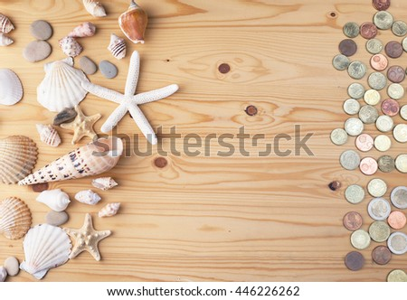 Shells, stones, starfish and coins on wooden background. Top view with copy space