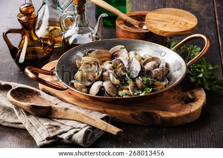 Shells vongole venus clams with parsley in copper cooking dish on dark wooden background  - stock photo