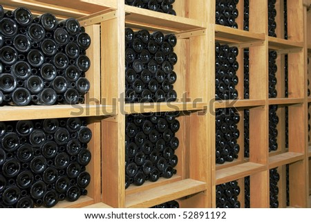 shelves with bottles in the cellar - stock photo