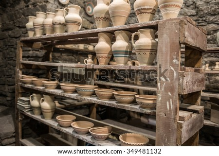 shelves with Ukrainian ceramics in potter workshop - stock photo