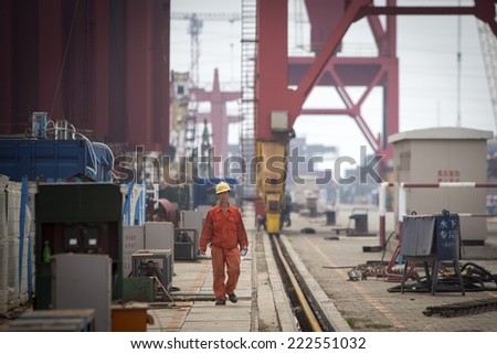 Shenzhen, China - August 6, 2014: Worker at a container cargo harbor is going for his lunch hour. - stock photo