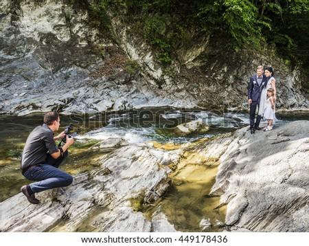 SHEPIT, KOSIV DISTRICT, IVANO-FRANKIVSK REGION, UKRAINE - July 12, 2015: photographer takes newlyweds near a mountain river - stock photo