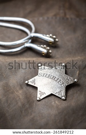 Sheriff badge and spurs on brown background - stock photo