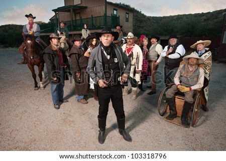 Sheriff in front of group in old American west theme - stock photo