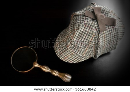Sherlock Holmes Deerstalker Hat And Vintage  Magnifying Glass On The Black Wooden Table Background. Overhead View.  Investigation Concept. - stock photo