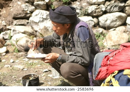 Sherpa Porter Eating with Hands - stock photo