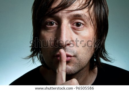Shh. Man holding a finger over his mouth making silent gesture. - stock photo
