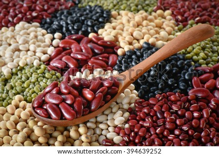 Shift Adzuki bean with wooden spoon on various legumes background