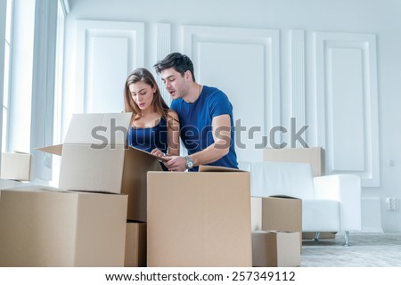 Shifting and moving to a new life. A girl and a guy holding boxes for moving the hands and looking inside while a couple in love standing at the window among boxes - stock photo