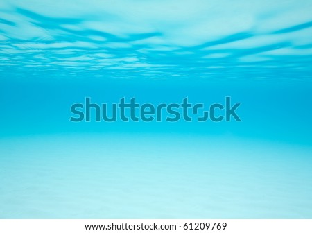 Shifting sand and moving water under the waves provides a blue abstract background - stock photo