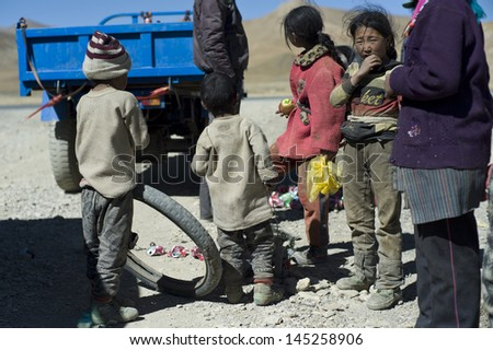 SHIGATSE,CHINA-OCT 11:Unidentified children feel excited when the relief team gives them fruit on October 11,2011 in Shigatse,China.Children in rural Tibet do not received enough food and education.