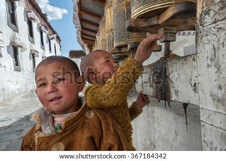 SHIGATSE - MAY 21: Young Tibetan pilgrim circle the holy Tashilunpo monastery on May 21, 2014 in Shigatse. Some devotees walk 108 times around the monastery to accumulate merit (karma). - stock photo