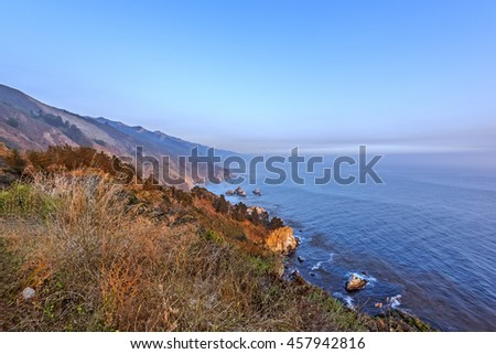 Shimmering blue, aquamarine sea and misty sky, the sun setting along steep sheer jagged cliffs of the Big Sur Coastline, while waves are splashing on huge rocks. Photographed near Carmel California. - stock photo
