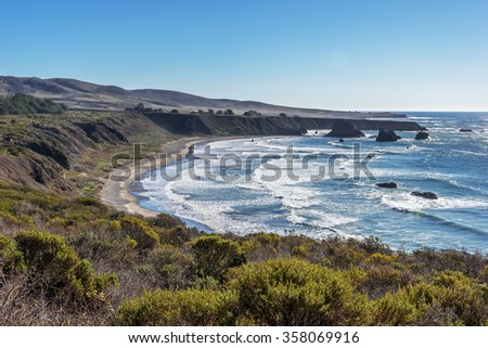 Shimmering reflective sunlight, blue skies, sandy beach & waves splashing along the rugged Big Sur coastline, viewed from jagged cliffs of Ragged Point by Highway 1 on the California Central Coast. - stock photo