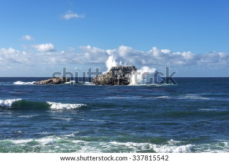 Shimmering sunlight and waves splashing on White Rock at Point Piedras Blancas with white caps along the rugged Big Sur coastline, near Highway 1 on the California Central Coast, near Cambria CA. - stock photo