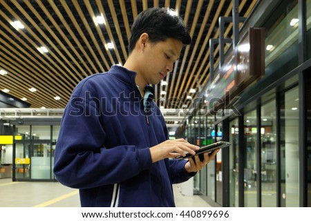 Shin-Hakodate-Hokuto train station,JAPAN-APRIL 6 ,2016: Businessman checking email on ipad while waiting the train at Shin-Hakodate-Hokuto station.