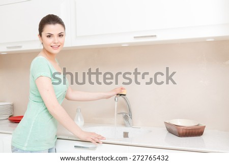 Shine of water. Pretty young woman standing in white kitchen and cleaning tap