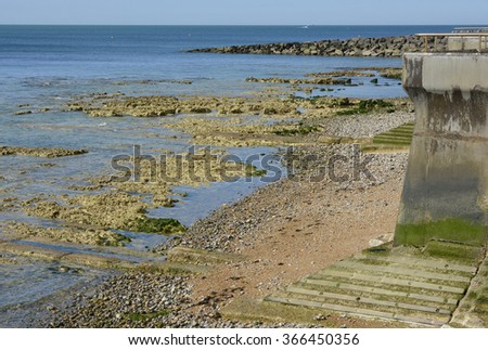 Shingle beach and rocks at low tide between Brighton Marina and Rottingdean, East Sussex, England - stock photo