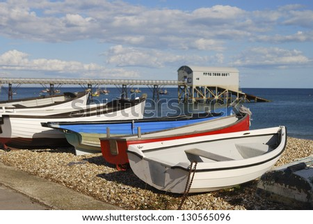 Shingle beach at Selsey. West Sussex. England. With lifeboat station in background (out of focus) and boats in foreground.