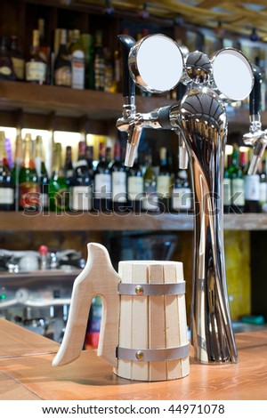 shining beer faucet with wooden mug in a bar - stock photo