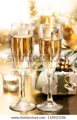 Shining champagne glasses with candles and gifts - stock photo