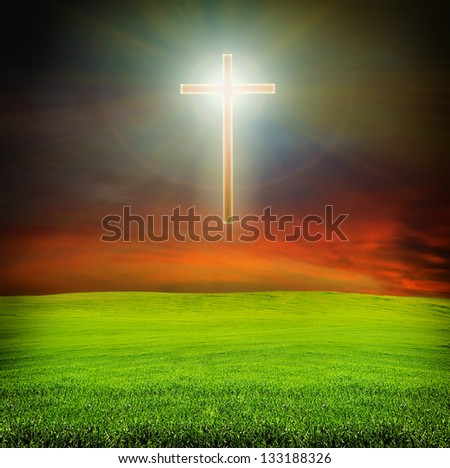 shining cross  over dark red sky and green field with grass - religion concept - stock photo