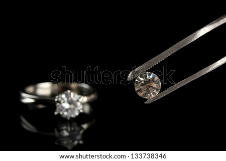 Shining crystal (diamond) in the tweezers and ring, on black background - stock photo