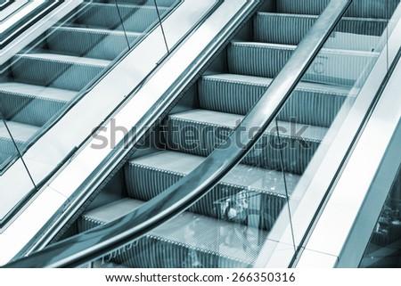 Shining metal escalator moving up, blue toned monochrome photo, selective focus with shallow DOF - stock photo
