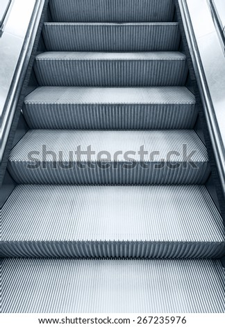 Shining metal escalator moving up, vertical monochrome photo with blue toning filter effect - stock photo