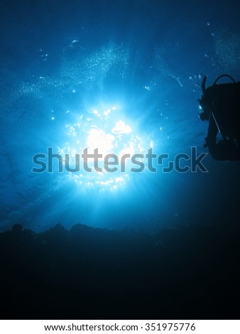 Shining sun seen from underwater with diver / Okinawa,Aka-island Japan