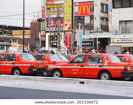 SHINKOIWA, TOKYO - JANUARY 7, 2014: Orange color taxis in front of Shinkoiwa railway station, downtown Tokyo, Japan.