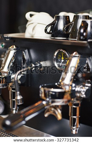 Shiny and clean coffee machine with the spout for steaming milk and the temperature guage clearly visible  - stock photo