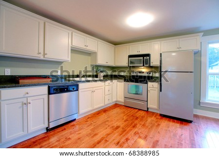 Shiny and new white kitchen with beautiful cherry hardwood floor. - stock photo