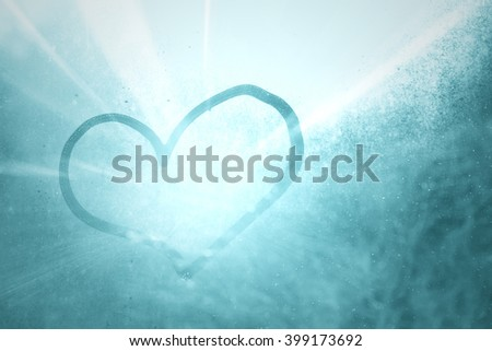 Shiny blue Love heart shape hand drawn on wet, frozen window pane with morning sunlight background. Selective focus used. - stock photo