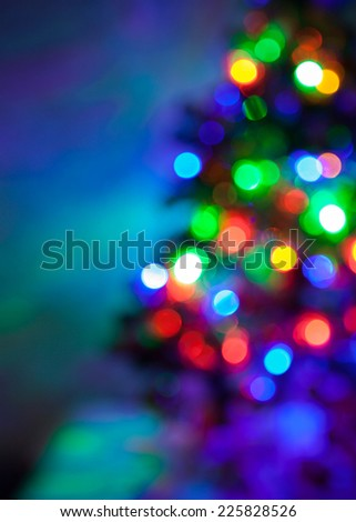 Shiny blur bokeh background with Christmas multicolored lights on the fir tree - stock photo
