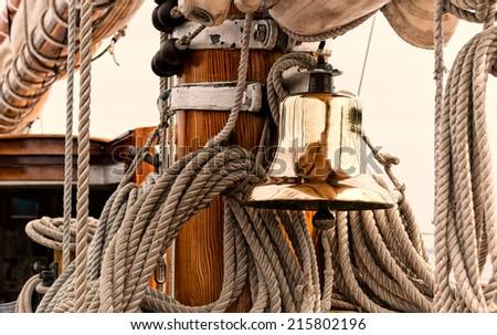 Shiny brass ship's bell on a vintage sailboat.  - stock photo