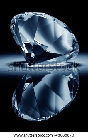 Shiny brilliant on a black reflective background - stock photo