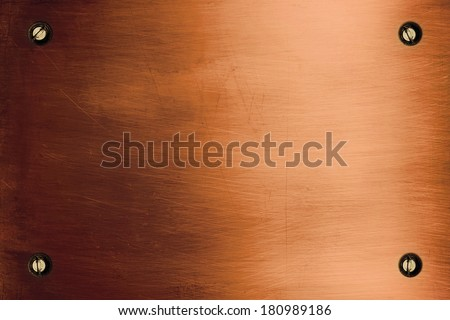 Shiny bronze metallic plate and screws - stock photo