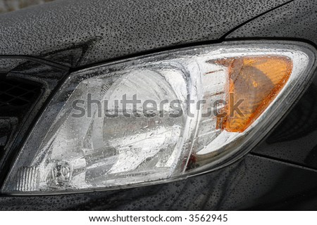 Shiny car with black paint. Water drops on the hood. Car lamp - stock photo