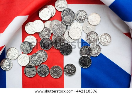 Shiny coins on Union Jack flags - British pound fell sharply after referendum - stock photo