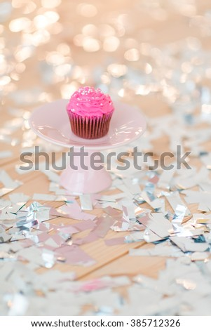 shiny confetti on the table and a plate with pink cupcakes - stock photo