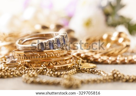 shiny gold and silver jewelery on white table