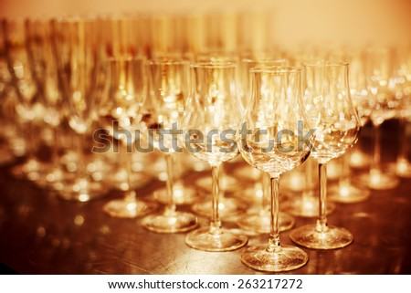 Shiny High Glasses Ready for Drinks. Restaurant, Catering Concept. Selective focus, shallow DOF. Image toned with gold colors. - stock photo